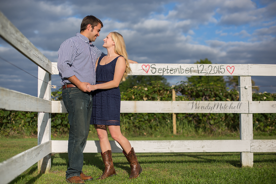 Engaged couple in front of white fence with wedding date in chalk | Buffalo Engagement Photography | Wendy Mitchell Photography