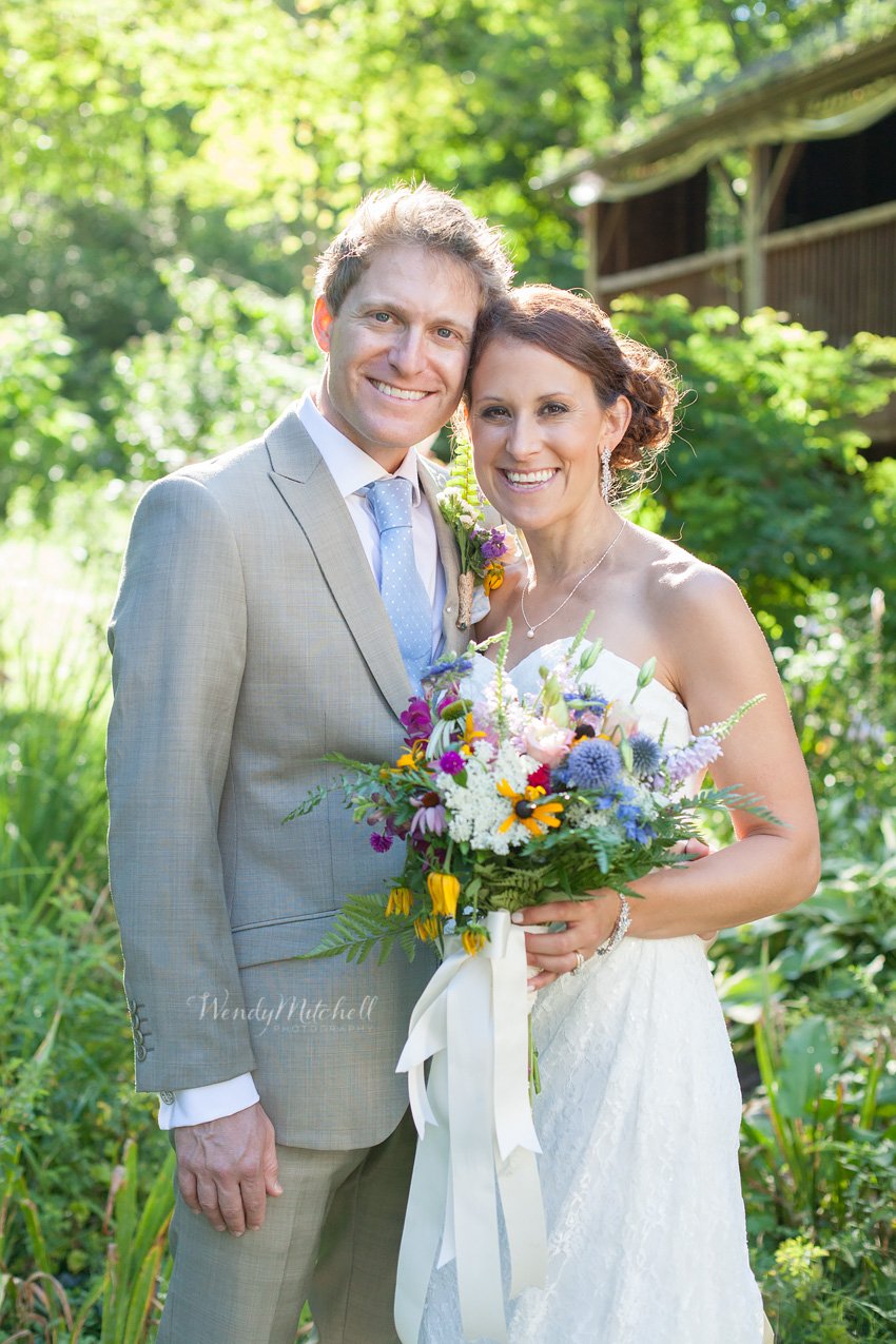 Bride & Groom smiling in small garden | Wendy Mitchell Photography