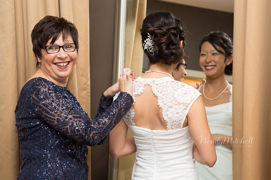 Groom's mom helping the bride with her dress | Mansion on Delaware | Wendy Mitchell Photography
