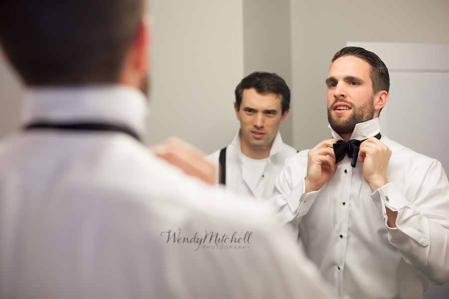 Groom looking in the mirror to tie his bow tie | Buffalo Wedding Photography | Wendy Mitchell Photography